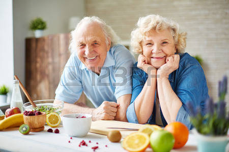 46149837-happy-senior-man-and-woman-looking-at-camera-in-the-kitchen